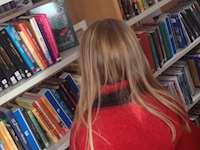 Barn vid bokhylla