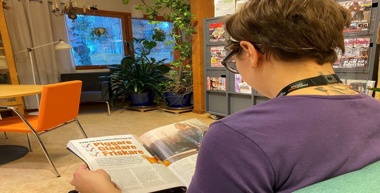 En kvinna sitter och läser en tidskrift.